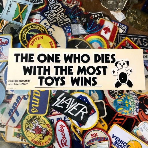 THE ONE WHO DIES WITH THE MOST TOYS WINS – REMOVABLE VINYL BUMPER STICKER