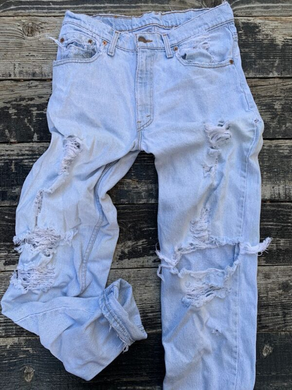 product details: RADICAL HEAVILY DISTRESSED, SHREDDED & THRASHED LEVIS 550 RED TAB JEANS photo